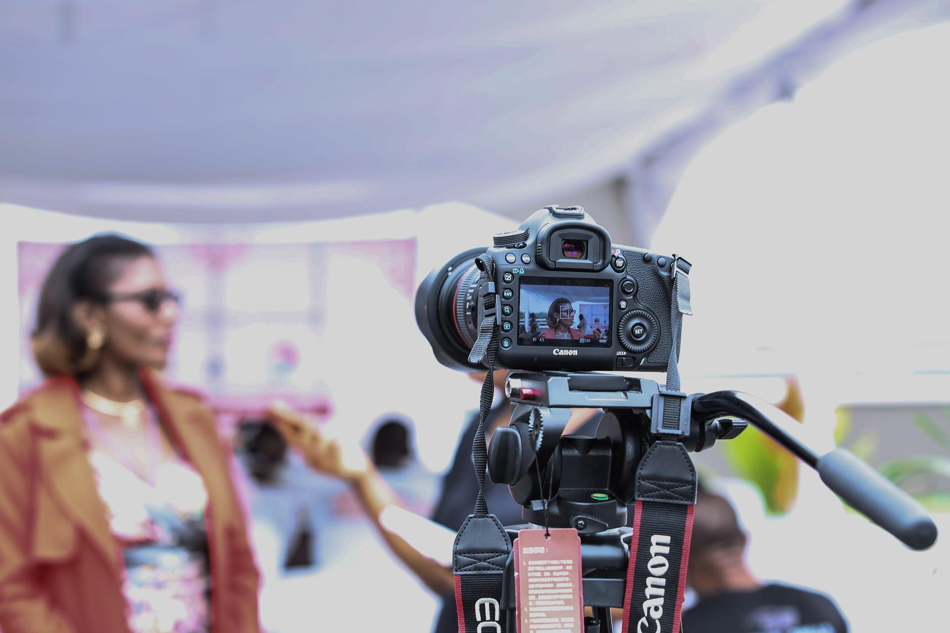 Videographer using a scissor lift platform to improve their angles.